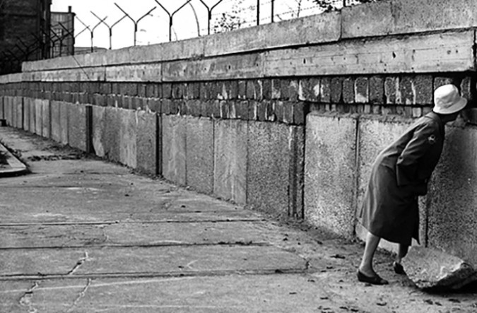 Woman looking through a hole in the Berlin Wall.